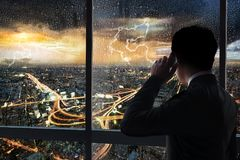 Business man in building. Business man using smart phone at glass window internal the building with night scene cityscape and rain storm background stock image
