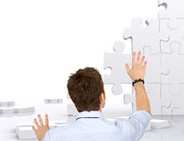 Business man building a puzzle Royalty Free Stock Photos