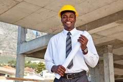 Business man in building site. African business man in a construction site wearing a hard hat and holding building plans Royalty Free Stock Photo
