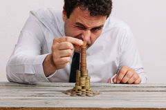 Business man building stack of money Stock Photography