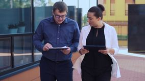 Business man and business girl go and discuss business project stock footage