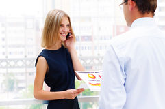 Business man and business woman discuss reports Royalty Free Stock Photos