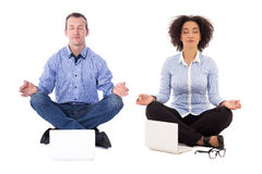 Business man and business woman sitting in yoga pose with laptop Royalty Free Stock Photos