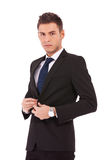 Business man buttoning his coat. Picture of a young business man buttoning his coat on whte background Royalty Free Stock Images