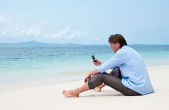 Business man calling by cell phone on the beach Stock Photo