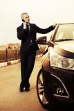 Business man calling on phone next to car Royalty Free Stock Images