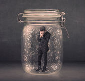Business man captured in glass jar with hand drawn media icons c Royalty Free Stock Photos
