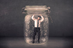 Business man captured in glass jar with hand drawn media icons c Stock Photos
