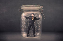 Business man captured in glass jar with hand drawn media icons c Stock Photo