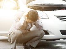Business man car breakdown. Worried Asian business man squatting beside his breakdown car, feel helpless Stock Image