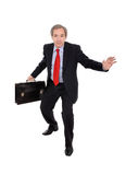 Business man carrying a briefcase. Mature businessman carrying a briefcase isolated on white royalty free stock images