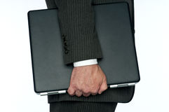 A business man carrying a computer Stock Photography