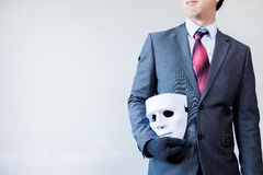 Business man carrying white mask to his body indicating Business Royalty Free Stock Images