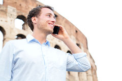 Business man on cell phone, Colosseum, Rome, Italy. Young businessman talking on smartphone outside smiling happy in casual shirt in front of Coliseum Royalty Free Stock Photo