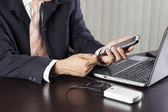 Business man charging his mobile phone Royalty Free Stock Photos