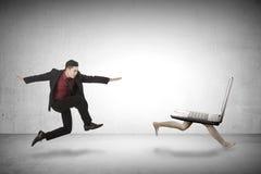 Business man chasing laptop Stock Photos