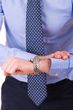 Businessman checking time on his wristwatch. Royalty Free Stock Image