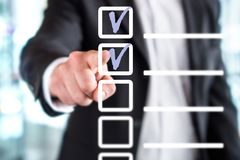 Business man with checklist and to do list. Man writing and drawing v sign check marks with hand and finger in square box. Project management, planning and royalty free stock photos