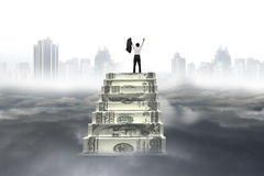 Business man cheer on money stairs with city landscape cloudscap Royalty Free Stock Image