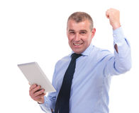 Business man cheers with tablet in hand Stock Photo