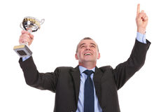 Business man cheers with trophy in hand Stock Image