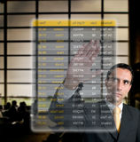 Business man choosing his flight at the airport. On a digital futuristic display Royalty Free Stock Photos