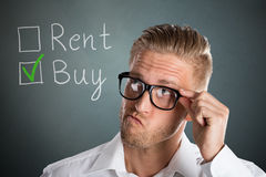 Business Man Choosing Rent Or Buy Option. Young Handsome Business Man Choosing Rent Or Buy Option For Real Estate Property Stock Photos