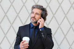Business man in the city making a phone call with smartphone holding to go cup of coffee or tea Stock Photography