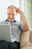 Business man with a clenched fist using a laptop Royalty Free Stock Photo