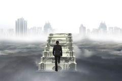 Business man climb on money stairs with city landscape cloudscap Stock Photos
