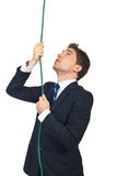 Business man climbing a rope Stock Image