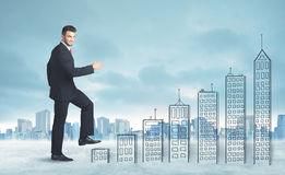 Business man climbing up on hand drawn buildings in city Royalty Free Stock Photos