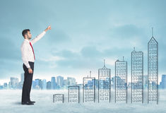 Business man climbing up on hand drawn buildings in city Stock Image