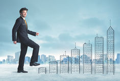 Business man climbing up on hand drawn buildings in city Royalty Free Stock Images