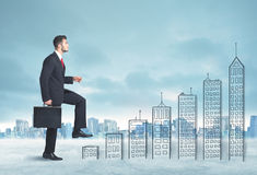 Business man climbing up on hand drawn buildings in city. Concept Royalty Free Stock Photography