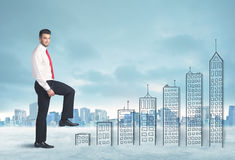 Business man climbing up on hand drawn buildings in city Stock Photo
