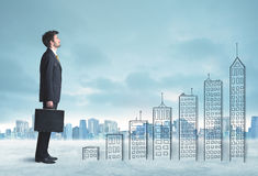 Business man climbing up on hand drawn buildings in city Stock Photos