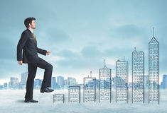 Business man climbing up on hand drawn buildings in city Royalty Free Stock Image