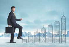Business man climbing up on hand drawn buildings in city Royalty Free Stock Photography