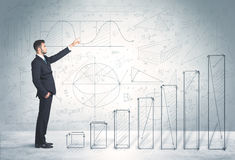 Business man climbing up on hand drawn graphs concept Royalty Free Stock Photo