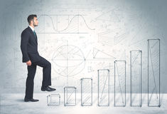 Business man climbing up on hand drawn graphs concept Stock Image