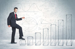 Business man climbing up on hand drawn graphs concept Stock Photo