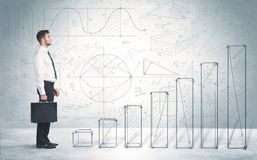 Business man climbing up on hand drawn graphs concept Stock Photos