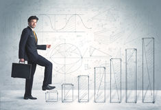 Business man climbing up on hand drawn graphs concept Stock Photos