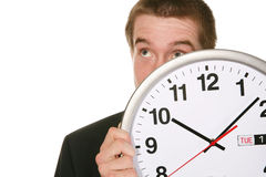 Business Man with Clock. A handsome business man hiding behind a clock Stock Images