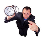 Business Man with Clock. A business man pointing to a clock isolated on white background Royalty Free Stock Photos