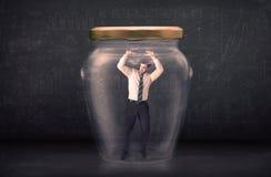 Business man closed into a glass jar concept Stock Photos