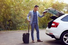 Business man closes car trunk stock photography