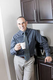 Business man at coffee break. Smiling businessman standing holding coffee cup in office kitchen stock image