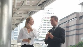 Business man with coffee cup and hamburger on sky walk in the morning stock footage
